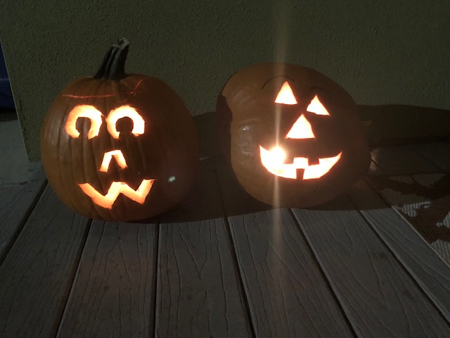 Two+carved+jack-o-lanterns+sit+on+the+front+porch+of+a+students+house.