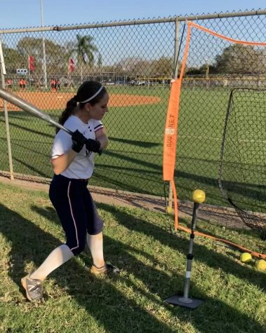 Sierra Bradow (12) takes practice swings off a tee. Bradow excelled in batting with a current average of .440, the highest on her team.